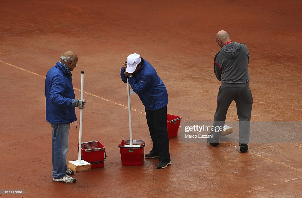 Ground staff mop the court after rain stopped play on day two of the Fed Cup World Group Play-Offs between Switzerland and Australia at Tennis Club Chiasso on April 21, 2013 in Chiasso, Switzerland.