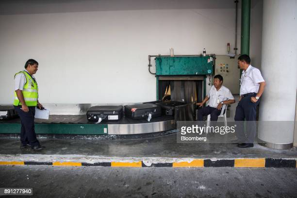 Ground staff observe luggage moving along a luggage carousel at Chiang Mai International Airport in Chiang Mai Thailand on Wednesday Dec 13 2017...