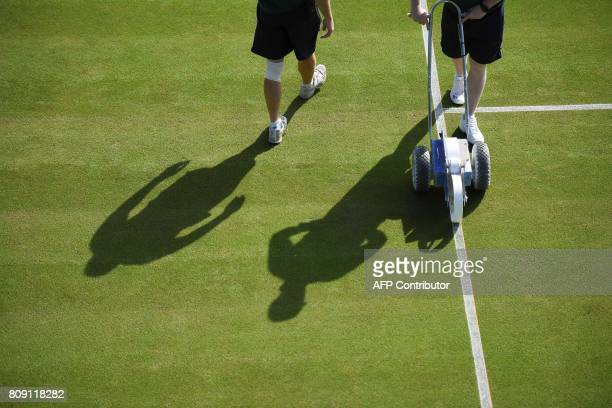 Ground staff prepare a court for play at The All England Lawn Tennis Club in Wimbledon southwest London on July 5 2017 on the third day of the 2017...