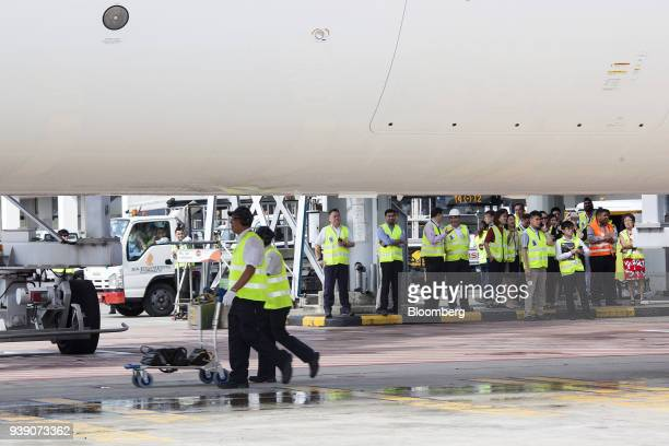 Ground staff prepare as a Boeing Co 78710 Dreamliner aircraft operated by Singapore Airlines Ltd stands at Changi Airport in Singapore on Wednesday...