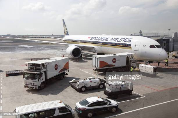 Ground staff prepare as a Boeing Co 78710 Dreamliner aircraft operated by Singapore Airlines Ltd stands docked to a passenger boarding bridge at...