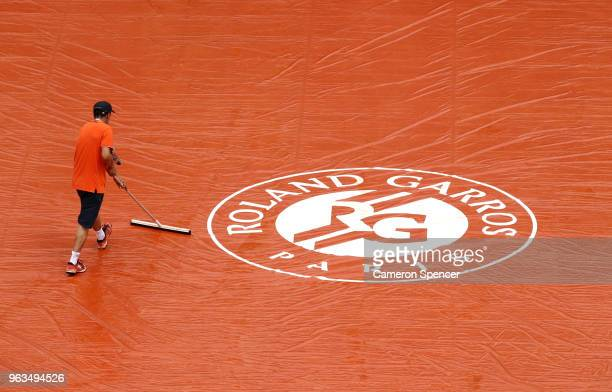 Ground staff prepare the court during a rain delay on day three of the 2018 French Open at Roland Garros on May 29 2018 in Paris France