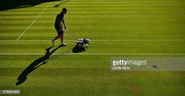 Ground staff prepare the grass on Court 19 ahead of play on day two of the 2015 Wimbledon Championships at The All England Tennis Club in Wimbledon...