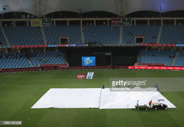 Ground staff pull the covers over the wicket area as rain sets in during the 3rd One Day International match between Pakistan and New Zealand at...