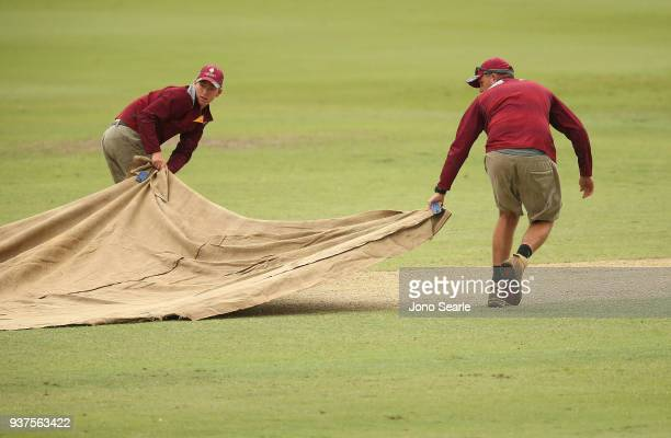 Ground staff put covers on the pitch during a rain delay during day three of the Sheffield Shield final match between Queensland and Tasmania at...