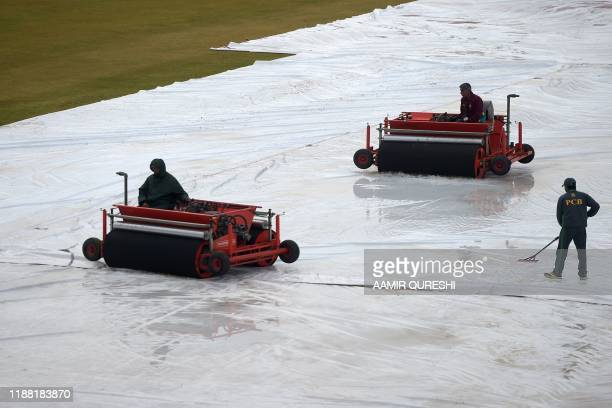 Ground staff remove rain water from the cricket pitch on the third day of the first Test cricket match between Pakistan and Sri Lanka at the...