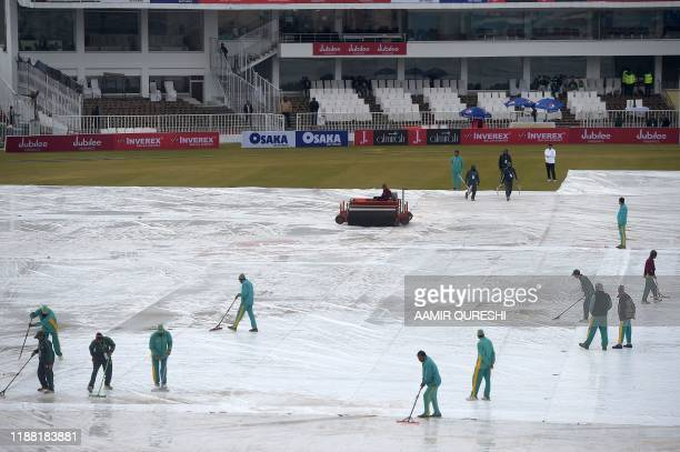 Ground staff remove rain water from the pitch during the third day of the first Test cricket match between Pakistan and Sri Lanka at the Rawalpindi...