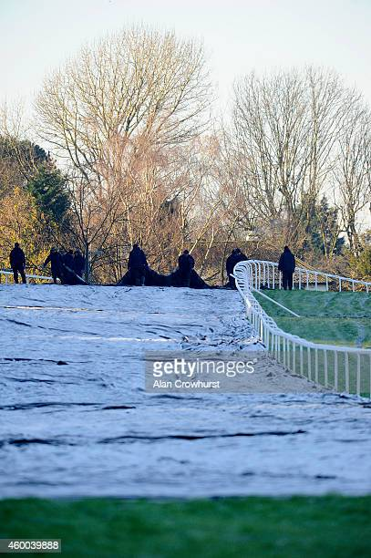 Ground staff remove the frost covers as a 1030 inspection takes place at Sandown racecourse on December 06 2014 in Esher England
