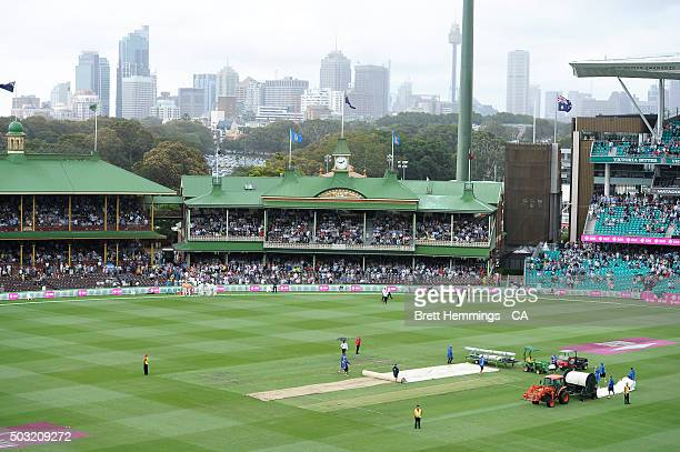 Ground staff rush to cover the pitch as rain begins to fall during day one of the third Test match between Australia and the West Indies at Sydney...