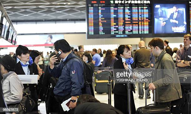 Ground staff speak to passengers as they queue up at check-in counters at Narita International Airport in suburban Tokyo on April 20, 2010. Some...