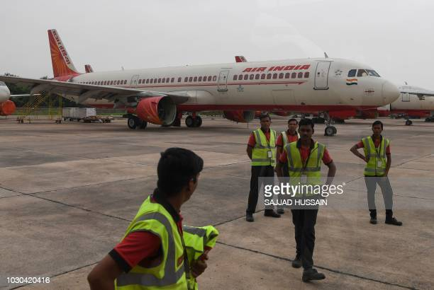 Ground staff stand next to an Air India plane at Indira Gandhi International Airport in New Delhi on September 10 2018