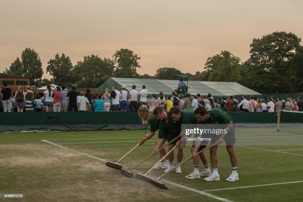 Ground staff sweep loose dirt along the baseline in the outside courts by the end of day four of the Wimbledon Lawn Tennis Championships at the All England Lawn Tennis and Croquet Club on July 6, 2017 in London, England.