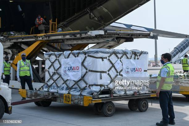 Ground staff unload Covid-19 coronavirus relief supplies from the US at the Indira Gandhi International Airport cargo terminal in New Delhi on April...