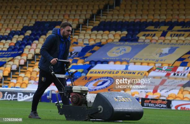 Ground staff work at the Field Mill stadium, home to Mansfield Town FC in Mansfield, northern England on October 26, 2020. - Football clubs outside...
