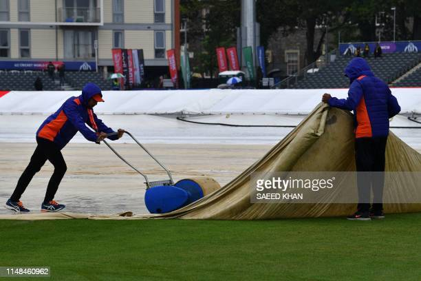 Ground staff work on the covers as rain delays start of play at the 2019 Cricket World Cup group stage match between Pakistan and Sri Lanka at...
