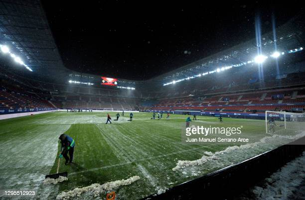 Ground staff work on the pitch to clear snow prior to the La Liga Santander match between C.A. Osasuna and Real Madrid at Estadio El Sadar on January...