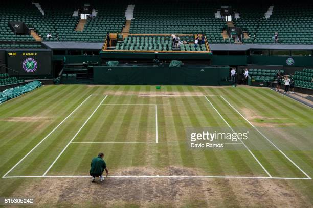 A ground staff works on Centre Court ahead of day thirteen of the Wimbledon Lawn Tennis Championships at the All England Lawn Tennis and Croquet Club...