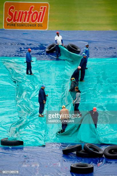 Ground staffs remove tarpaulins from the crease at the Newlands Stadium in day three of the First Test cricket match between South Africa and India...