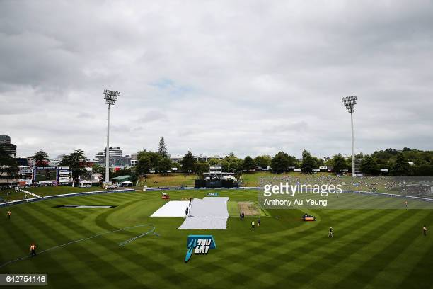Ground staffs try to pull off the covers as clouds hang above the field ahead of the First One Day International match between New Zealand and South...