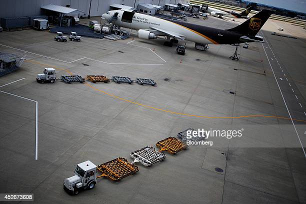 Ground support vehicles move alongside United Parcel Service Inc jet freighters on the tarmac during the afternoon sort at the UPS Worldport hub in...