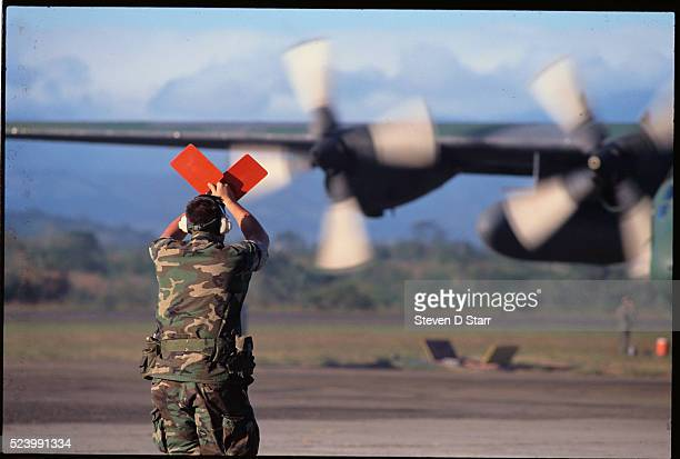 Ground traffic controller signals to a military airplane at an airport in Panama. The United States invaded Panama in 1989 to bring leader Manuel...