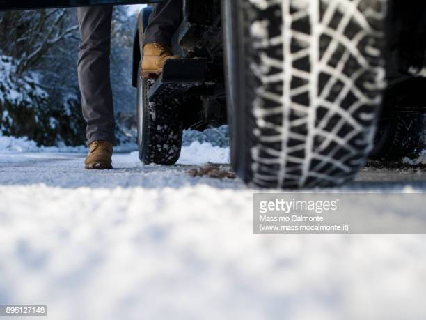 ground view of a jeep tyre on a snow-covered road - road salt stock pictures, royalty-free photos & images