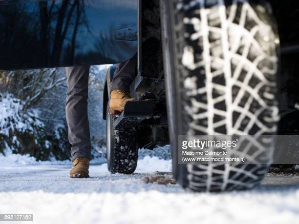 ground view of a jeep tyre on a snow-covered road - movendo um veículo - fotografias e filmes do acervo