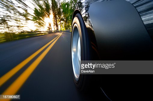 ground view of car tire speeding along country road sunset