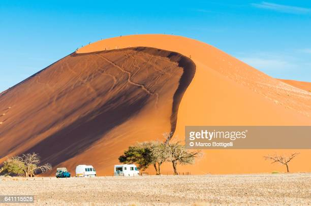Ground view of the world famous Dune 45 with tourists. Sossuvlei, Namibia.