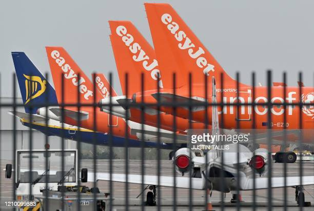 Grounded RyanAir and EasyJet aircraft are pictured on the apron at London Luton Airport north of London on April 16 2020 EasyJet will likely keep its...