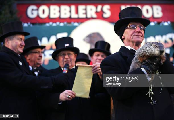 Groundhog cohandler Ron Ploucha holds Punxsutawney Phil as 'His Protector' Bob Roberts reads out the proclamation after Phil didn't see his shadow...