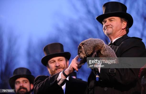 Groundhog handler Ben Hughes pets Punxsutawney Phil while cohandler John Griffiths holds him after he saw his shadow predicting 6 more weeks of...