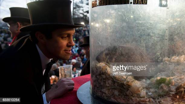 Groundhog handler Dan McGinley looks at Punxsutawney Phil after he saw his shadow predicting six more weeks of winter during 131st annual Groundhog...