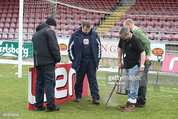 Groundmen Paul Knowles and Pete Spraggon use hot water to melt ice on the pitch as Jazon Hawthorn and referee Jon Moss look on look prior to the...