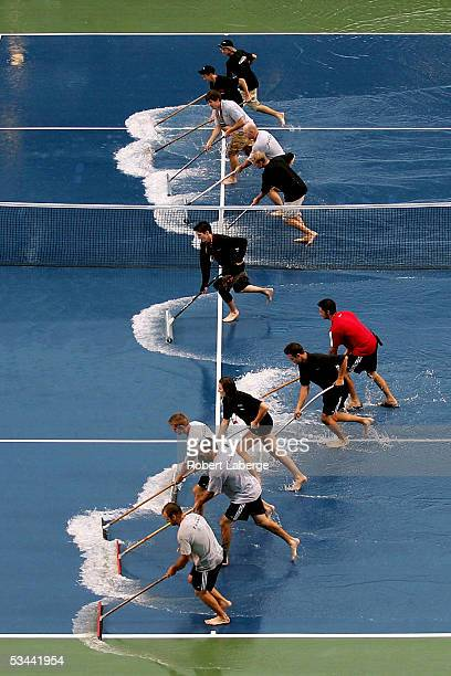 Grounds crew clear the court of water after torrential rains delayed the game between Amelie Mauresmo of France and Nadia Petrova of Russia during...