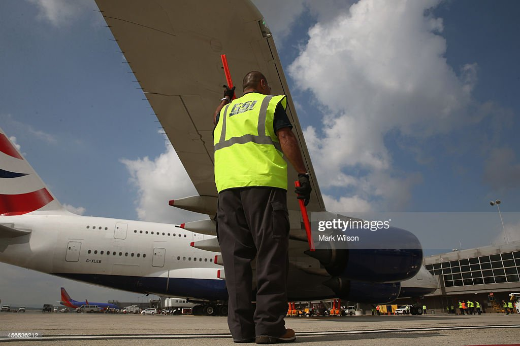 A grounds crew helps guide the British Airways' new super jumbo Airbus A380 as it taxies to its gate at Washington Dulles International Airport October 2, 2014 in Dulles, Virginia. British Airways introduced the first Airbus A380 nonstop service between London Heathrow and Washington Dulles International Airport.