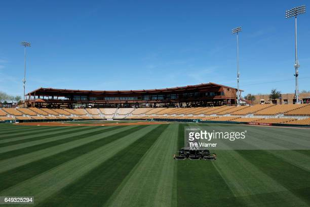 A grounds crew member mows the outfield before the spring training game between the Los Angeles Dodgers and the San Francisco Giants at Camelback...