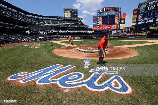 A grounds crew member paints the Mets logo on the field during the 84th MLB AllStar Game on July 16 2013 at Citi Field in the Flushing neighborhood...