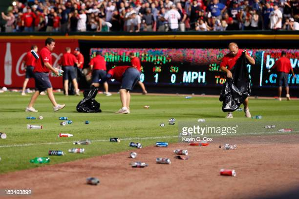 Grounds crew members clean up bottles and cups thrown by fans after the home fans disagree with an infield fly ruling on a ball hit by Andrelton...