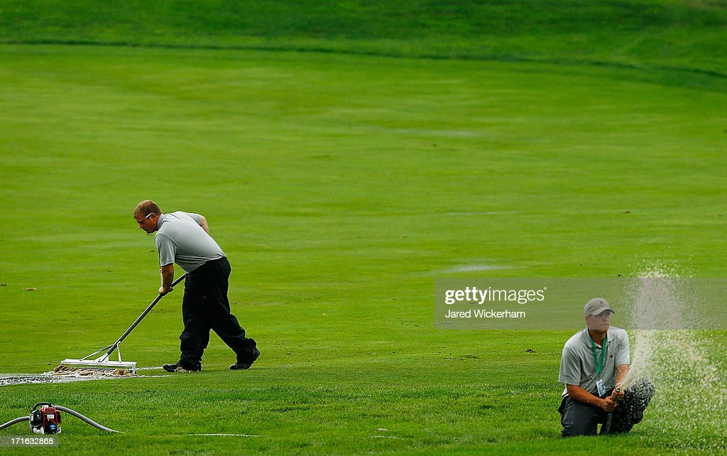 Grounds crew members squeegee the fairway following a rain delay during the first round of the 2013 Constellation Senior Players Championship at Fox Chapel Golf Club on June 27, 2012 in Fox Chapel, Pennsylvania.