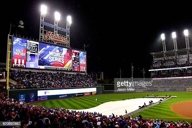 Grounds crew put a tarp on the field as the game is delayed due to rain before the start of the 10th inning between the Chicago Cubs and the...