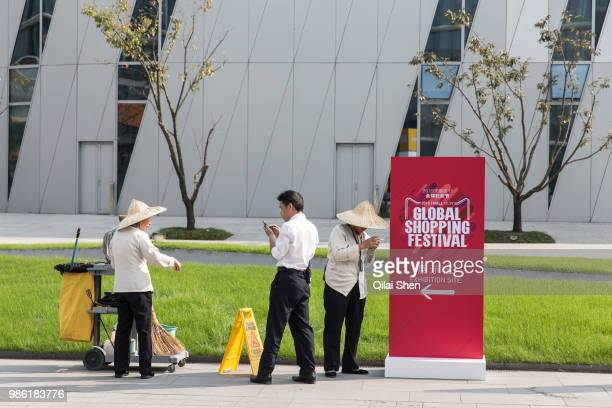 Grounds crew stands near a sign at a event promoting the 1111 shopping festival at the Alibaba Group Holding Ltd headquarters in Hangzhou China on...