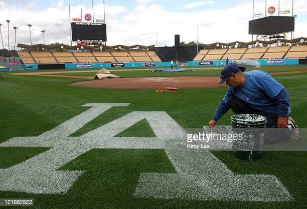 Grounds crew worker Chris Romo paints the Los Angeles Dodgers logo at Dodger Stadium in Los Angeles Calif on Wednesday March 29 2006The stadium which...