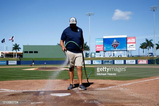 Grounds crew workers clean up the field after the Grapefruit League spring training game between the Washington Nationals and the New York Yankees at...