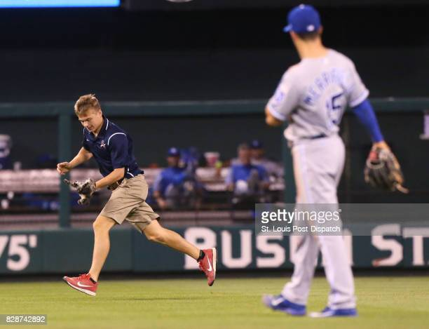 A grounds keeper retrieves a small cat that ran across the outfield in the sixth inning of a game between the St Louis Cardinals and the Kansas City...