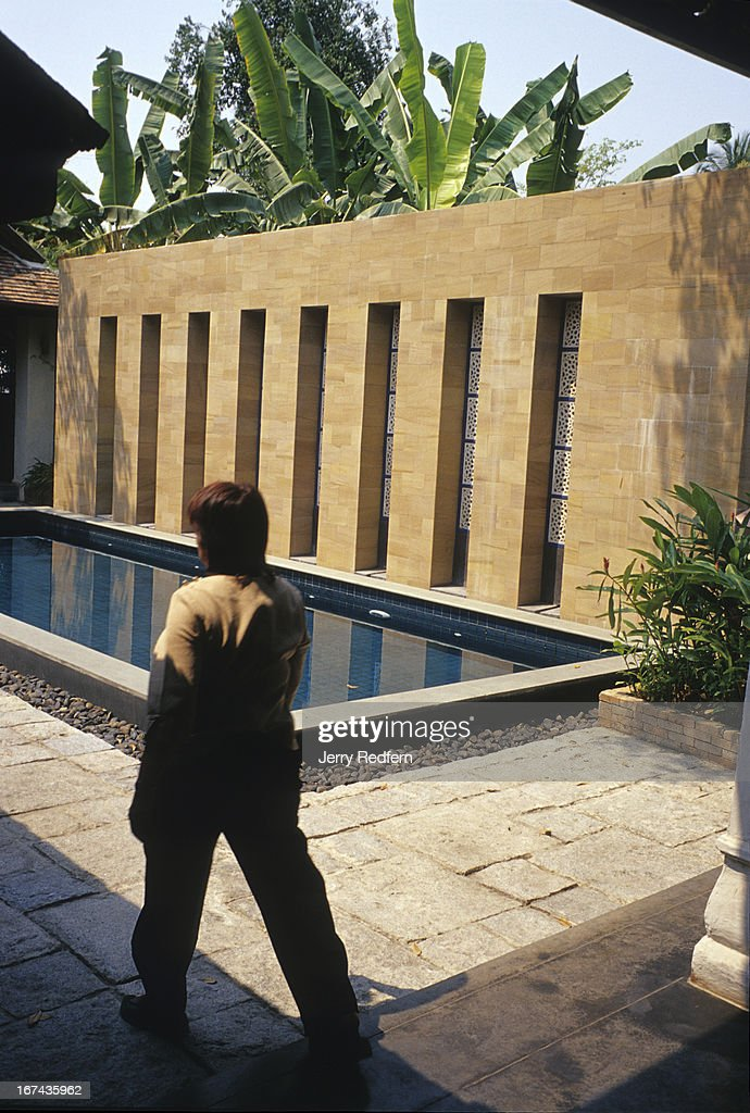 A grounds keeper walks past the small swimming pool of the Baan Tazala Hotel in Chiang Mai. The high-end boutique hotel mixes old and new Thai and European styles..