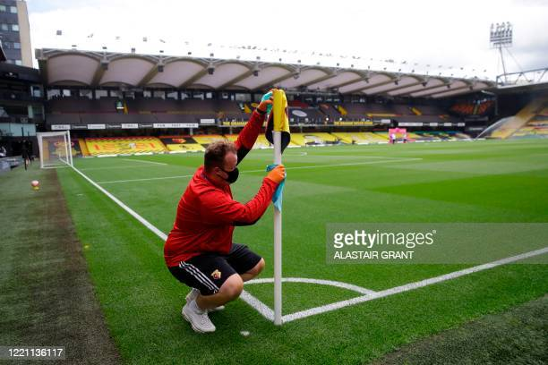 Grounds man cleans a flagpole before the English Premier League football match between Watford and Leicester City at Vicarage Road Stadium in...