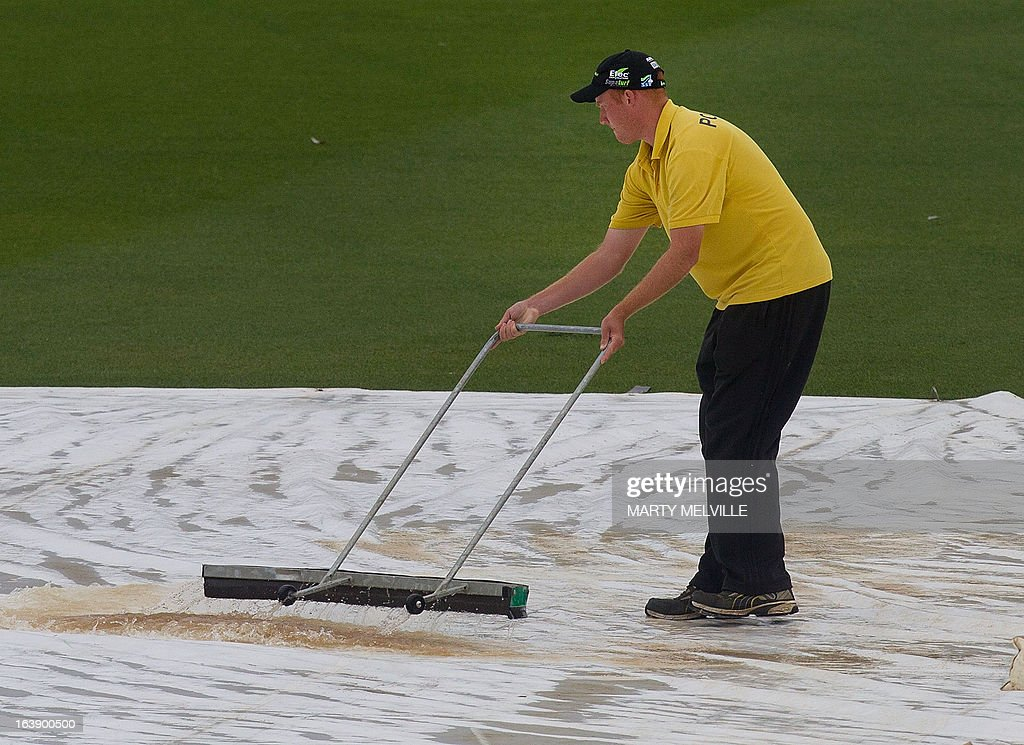 Grounds staff push the water off of the covers as rain halts all play during day five of the international cricket Test match between New Zealand and England played at the Basin Reserve in Wellington on March 18, 2013. AFP PHOTO / Marty MELVILLE