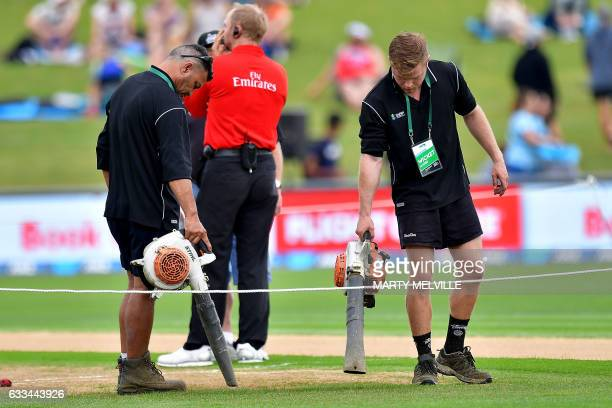 Grounds staff use leaf blowers to dry the wicket as rain delays the start of the 2nd oneday international cricket match between New Zealand and...
