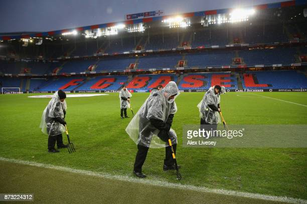 Grounds staff work on a water logged pitch prior to the FIFA 2018 World Cup Qualifier PlayOff Second Leg between Switzerland and Northern Ireland at...